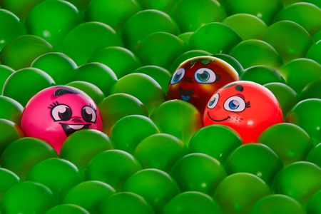 A pink happy ball with brown eyes is very happy and communicate with An orange one and a brown one , in middle of green balls without personality