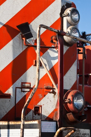 Detail of a front heavy diesel north american locomotive, with 3 headlights, 2 brooms, red and white stripes with color cracks Stock Photo - 20555949