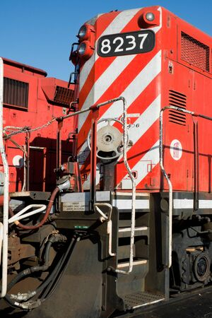 hand brake: Detail of a front heavy diesel north American locomotive, with headlights, red and white stripes, stairs, connections, hand brake wheel    Editorial