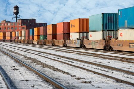 Industrial railway terminal in winter with container transport wagons, rails, old brick building, snow and a water tower Editorial