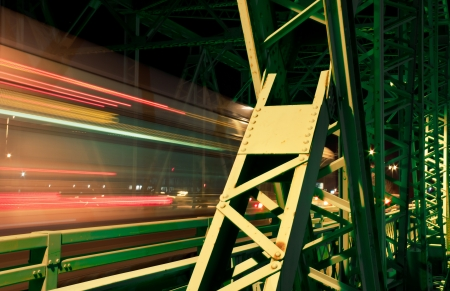 Old metal bridge in the night lights In the right part of the image is the metal structure and in the left part are the lights of the passing by cars   Stock Photo