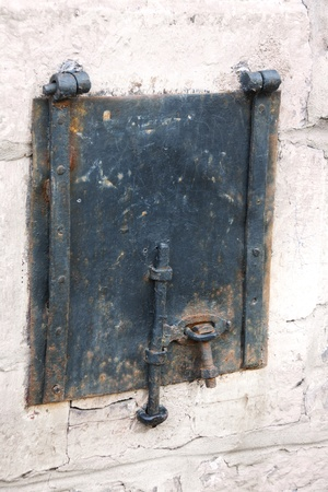 Ancient metal little door knob with 2 hinges on a wall Stock Photo