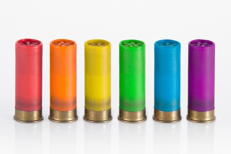 six hunting cartridge in line, each one in a colour of the rainbow isolated in white