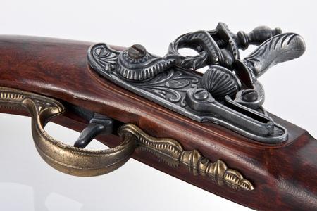 flint gun: Cerca gatillo y disparar mecanismo de una antigua pistola de pedernal, aislado en blanco