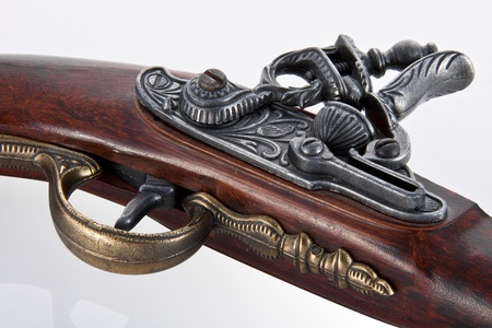 Close up trigger and firing mechanism of an ancient flint pistol, isolated in white