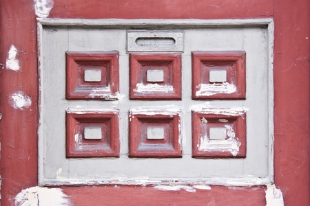 Detail of an vintage door how had a letters window and a white and red square decoration