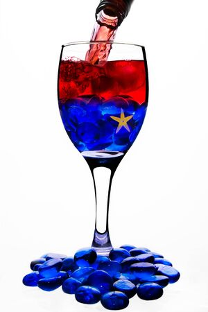 A wine glass shooted in white background, the glass has a strange cocktail half blue - half red  In the botton half  blue  is a yellow ocean star