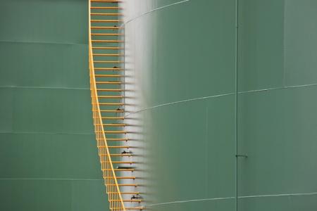 Vertical yellow metal stairs between two huge green gas tanks