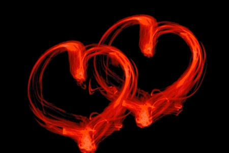 Two red light draw hearts against a black background