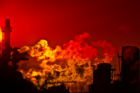 Flames and smoke against a red sky and industrial facilities Stock Photo