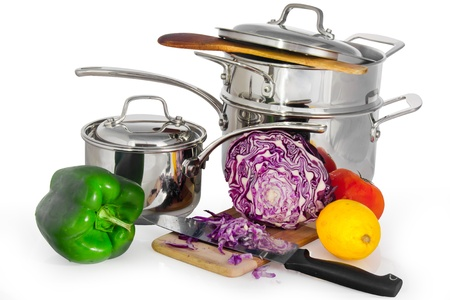 Steam shiny metal saucepan complex isolated in white with vegetables and fruit ready to be chopped with a knife on a piece of wood