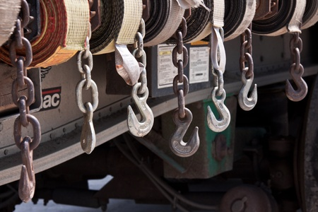 Seven metal hooks, chains and straps ready to be used on a trailer