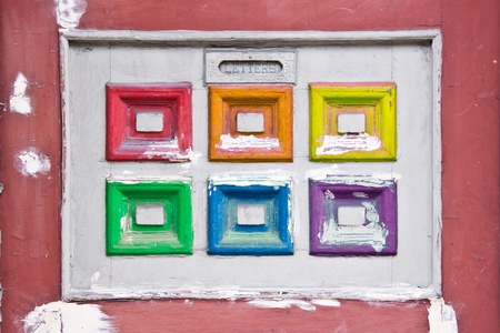 Detail of an vintage door how had a letters window and a white and rainbow square decoration, each square in another color of the rainbow Stock Photo - 20832481