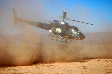 helicopter taking off from a dusty terrain