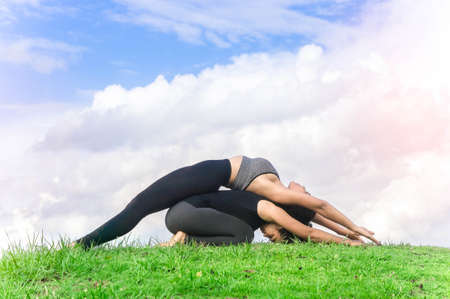 two persons only: Woman twin practicing  yoga relax in nature and blue sky background Stock Photo