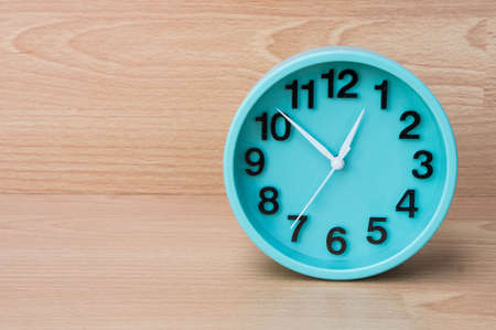 oclock: Green clock on wood background , Clock to tell time Create a plan to manage the hustle of life or work.