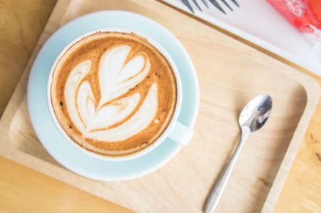 cappuccino foam: coffee heart cup and cake on wood table in coffe shop cafe Stock Photo