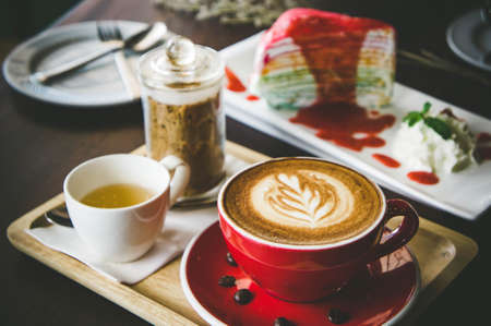 aroma coffee red cup latte art and tasty cake on wood table in coffee shop with vintage dark tone and copy space Stok Fotoğraf - 84184298