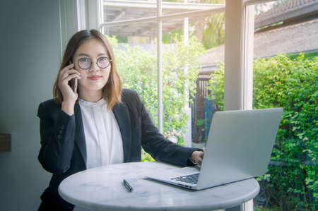 make summary: working woman , young business woman asian style talking on smart phone and working  sand data, account, analytical summary, with notebook and internet make the work easy, fast, smart and successful