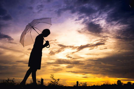 The girls silhouette style walking alone outdoor and umbrella in her hand with cloudy skies and evening sun