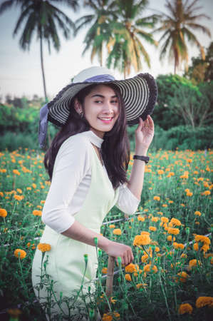 beautiful woman asia style on yellow flower garden and looking smile happy time on the day