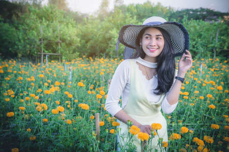 beatiful woman asia style on yellow flower garden and looking smile happy time on the day