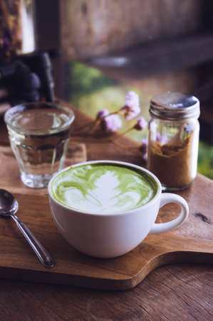 green tea hot drink latte white cup on wood table aroma relax time in coffee shop