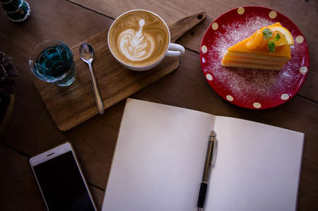 Top view coffee latte aroma cup and tasty christmas cake relaxtime waiting for idea on paper note on wood table in cafe coffee shoop Stock Photo