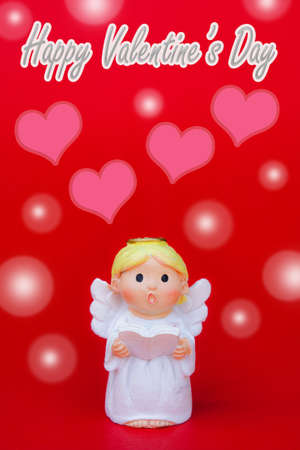 The cupid doll on red valentine background and pink heart-shaped on red background happy valentines day concept, the cupid on valaetines day
