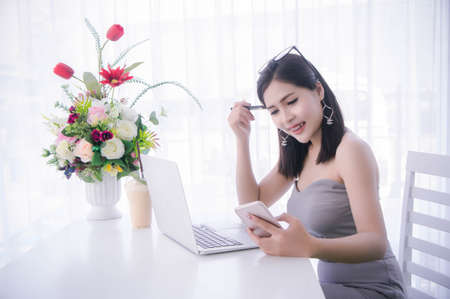 smart girl's using smart phone and working on laptop ,happy time on work, smile and laughing time work , workingwomen get think about work Imagens