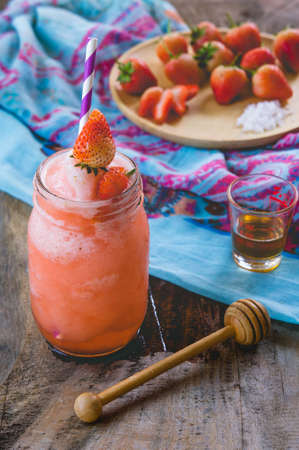 Strawberry smoothie juice ,  on topping honey tasty for summer on wood table , sweet water juice for health