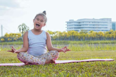 Healthy yoga girls and concentrate in the park , kid Yoga Practice for Health in the nice day , yoga kid