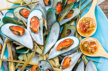 Steaming mussel With delicious sauce on dish with wood table seafood style