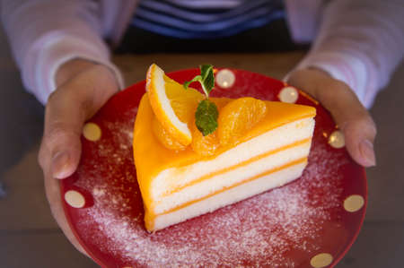 Tasty orange fruit cake on red christmas patt dish for ready to eat
