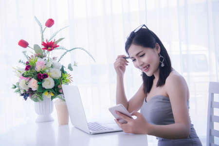 smart girl's using smart phone and working on laptop ,happy time on work, smile and laughing time work , workingwomen get think about work Stock Photo