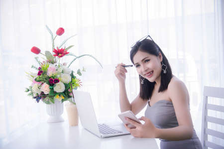 smart girls using smart phone and working on laptop ,happy time on work, smile and laughing time work , workingwomen get think about work