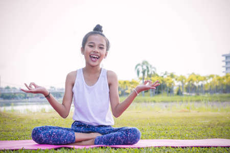 Girls practicing yoga in the park  Strengthens concentration and health , Yoga for kid have fun Meditation activities for children Stock Photo