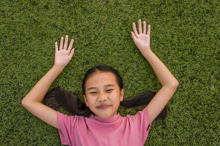 kid asian girls lie leisurely on the Lawn floor and smile looking at Stock Photo