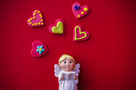 Cupid doll and heart-shaped on red background Stok Fotoğraf