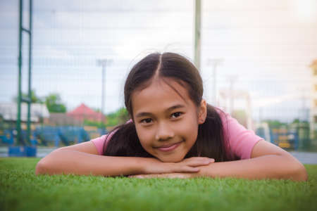 kid asian girls lie leisurely on the Lawn floor and smile looking at Stok Fotoğraf