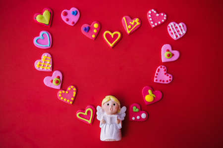 Cupid doll and heart-shaped on red background Stock Photo
