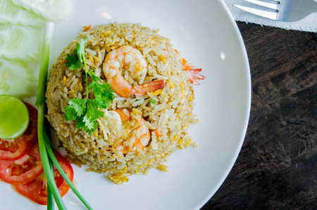 Fried rice with shrimp in a white dish on wood table in thai food style