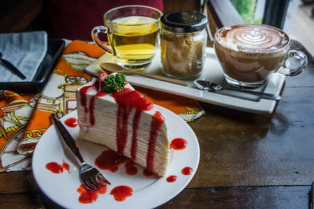 strawberry crape cake on wood table in coffee shop , dessert tasy cake