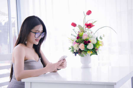 Girls looking and enjoy smartphone in her hand and laugh sitting on chair in the room