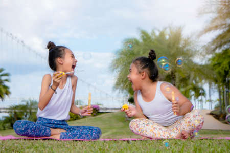 Girls happiness funny soap bubble in the park ,Laughing happy with the learning of friendship , lovely sister