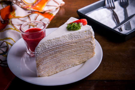 strawberry crape cake on wood table in coffee shop