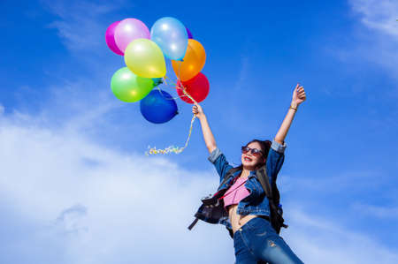 Jumping girl holds balloons on the sky background