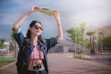 Sunshine in the summer and women traveler hold a map to protect the sun