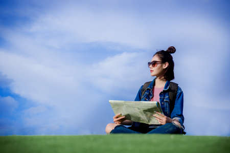 Woman traveler sit down on green grass and holds the map