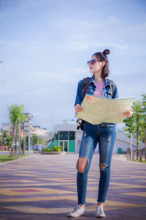 traveler girl holds the map and looks for destination